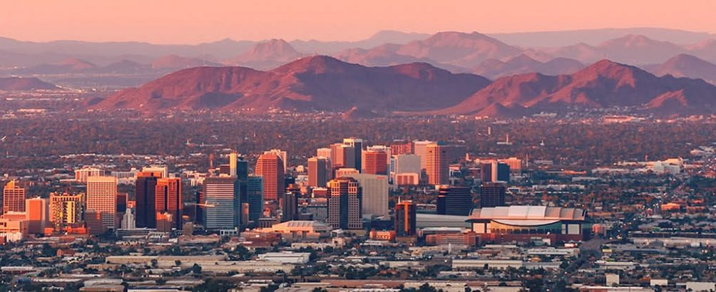 An aerial view of the Phoenix cityscape and the surrounding mountains at dawn.