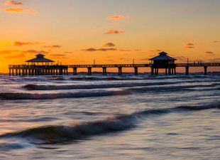 A sunset over a fishing pier in the Gulf of Mexico, Fort Myers, FL with calm waves on the beach.