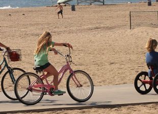 A family rides bicycles and tricycles along the beach boardwalk in Los Angeles on a sunny day, showing a lifeguard station and sunbathers in the background next to the Pacific Ocean.
