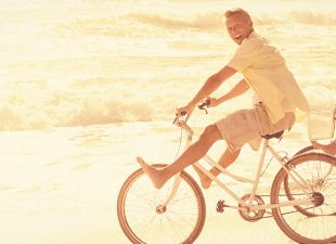Happy couple on a beach bike ride.
