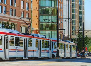 White tram with red and blue stripes moves through downtown Salt Lake City, Utah with business buildings in the background on a sunny day