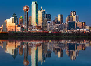 A panoramic view of the Dallas, Texas, city skyline reflecting on the Trinity River at sunset on a warm evening.