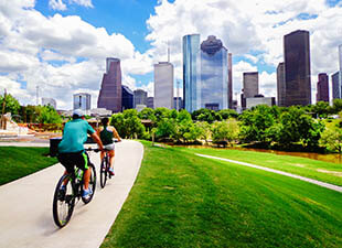 A couple rides along a bike path in Houston, Texas, on a warm and sunny afternoon.