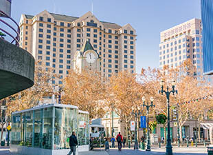 A street-level view of downtown San Jose buildings on a clear afternoon.