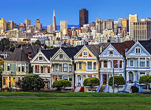 "Distant view of Alamo Square and the ""Painted Ladies"" houses in San Francisco on a sunny day."