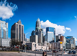 Panoramic view of Charlotte, North Carolina cityscape under a sunny blue sky with white clouds.