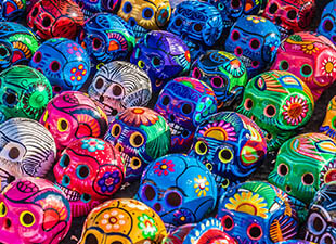 A close-up image of colorful traditional Mexican ceramic skulls celebrating Day of the Dead (Dia de los Muertos) on display at a market in Mexico.