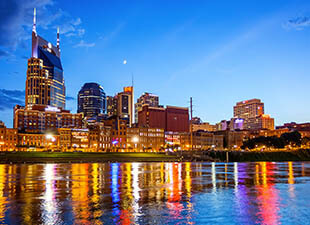 The illuminated downtown Nashville, Tennessee, cityscape is colorfully reflected in the Cumberland River at dusk on a summer evening.