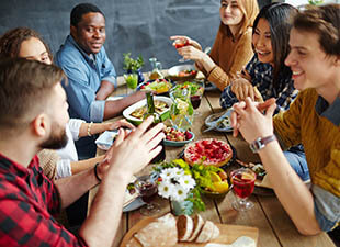 A group of diverse friends talk and laugh as they sit at a long wooden table covered with food during a Friendsgiving celebration on a bright afternoon.