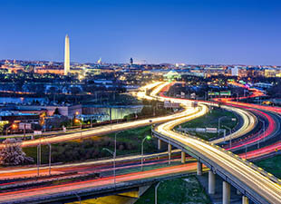 A long exposure image of light trails of cars on various freeways make yellow and pink lines on the roads in front of the skyline of Washington D.C. on a summer evening.