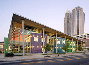 A shot of The Joe and Joan Martin Center illuminated with the city sky scrapers of Charlotte, North Carolina shown in the background at dusk on a warm summer evening