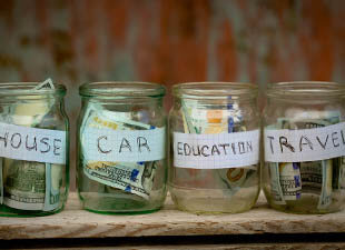 Four glass jars with dollar bills stuffed inside sit on a ledge labeled 'House,' 'Car,' 'Education,' and 'Travel.
