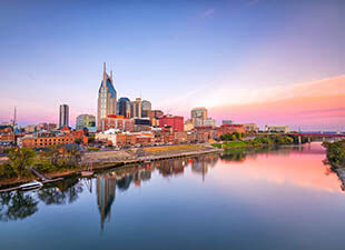 The Nashville, Tennessee downtown skyline is reflected off of the waters of the Cumberland River on a warm, clear summer evening during a pastel pinks and orange sunset.