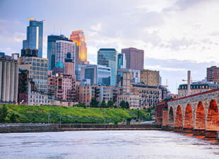View of Minneapolis, Minnesota from across the river on a partly cloudy day at sunset.