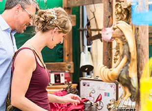 A man in a dress shirt and woman in purple tank top look at antiques and unique items at a flea market in Newark, New Jersey.