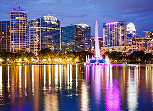The Orlando city skyline reflecting off of Lake Eola on a cloudy night shows the bright and colorful lights of Orlando