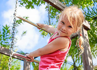 A young girl with blonde pigtails climbs a ladder under a blue sky and leafy green trees on a warm morning at Pullen Park in Raleigh, North Carolina.