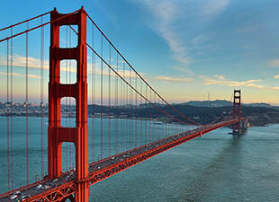 The Golden Gate Bridge in San Francisco glows in the evening sun on a summer day.