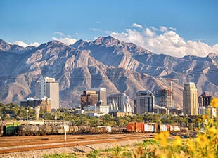 Panoramic shot of downtown Salt Lake City, Utah from across train tracks with one train on them, with mountains in the background on a sunny day under blue sky.