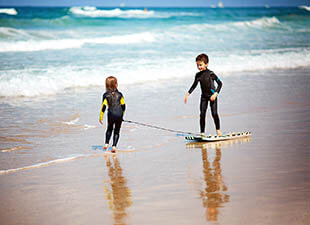 Two young kids in wetsuits play on the shore with a boogie board while enjoying a family vacation at West Palm Beach on a sunny, summer day, with the waves of the ocean rolling in the background.