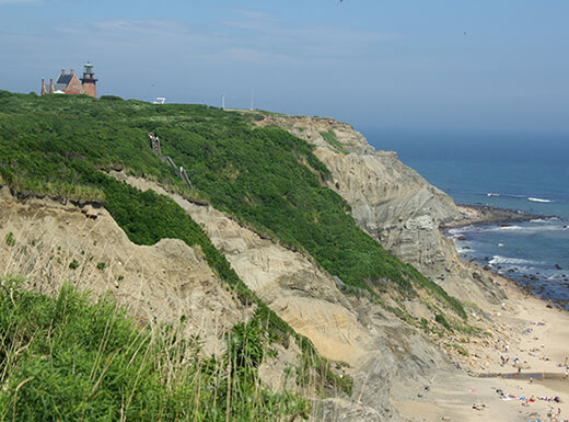 A lighthouse sits on top of the steep, grassy cliffs of Mohegan Bluffs, overlooking a white sandy beach and the ocean at Block Island, Rhode Island.