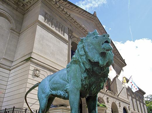View from below of a opper, turquoise Lion statue outside of the Field Museum in Chicago, an impressive stone building on a sunny day.