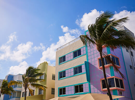View of the Miami Beach Ocean Drive lined with white Art Deco buildings with colorful trim under blue sky with palm trees swaying.