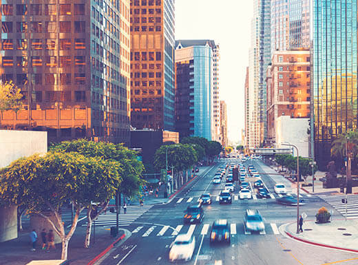 A view of traffic in downtown Los Angeles on an early morning, with the sun reflecting off of building windows.