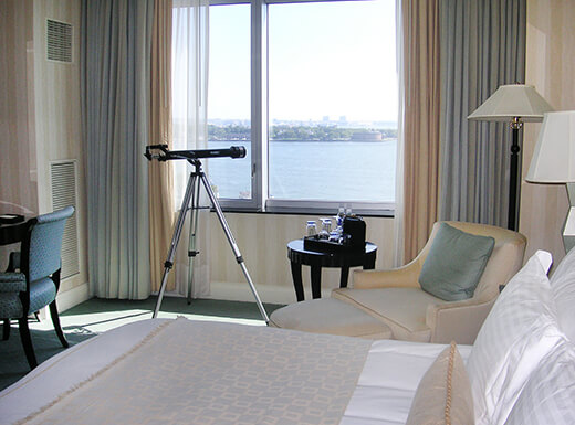 Interior view of a hotel room with a white linen bed, chair, and telescope near a window that overlooks the Statue of Liberty and Hudson River.