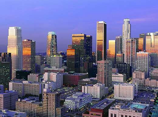 An aerial view of the city of Los Angeles, California, showing skyscrapers getting hit with the last rays of sunlight against a dark purple sky at sunset.