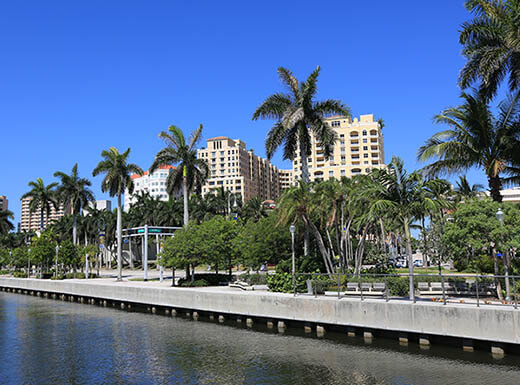 Clematis docks in downtown West Palm Beach on a sunny day shows the water of Lake Worth, lined with palm trees with buildings in the background