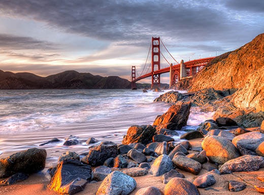 The Golden Gate Bridge from a distance on cloudy day as the golden light of sun hits the rocks on the shoreline in San Francisco.