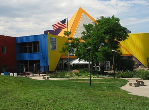 The Children's Museum of Denver is a colorful yellow, blue, orange, red, and green building with a triangular peak and large grassy area in Denver, Colorado.