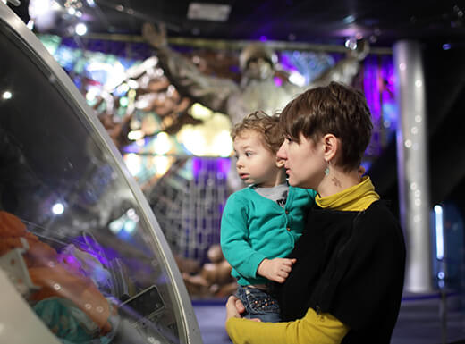 A woman wearing a black and yellow shirt holds a young boy wearing a green shirt in her arms as they examine an exhibit at the Wings Over the Rockies Air & Space Museum in Denver.