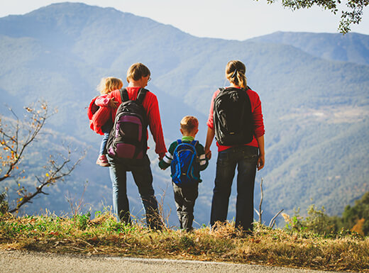 A family of four wearing backpacks and standing in the grassy brush by a hiking trail looking out over the Rocky Mountains in the distance.