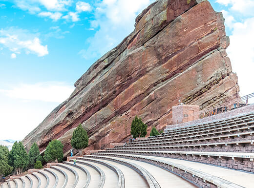 Rows of curved seating areas lead to a red rock tower with a bright blue sky at Red Rocks Amphitheatre near Denver, Colorado.
