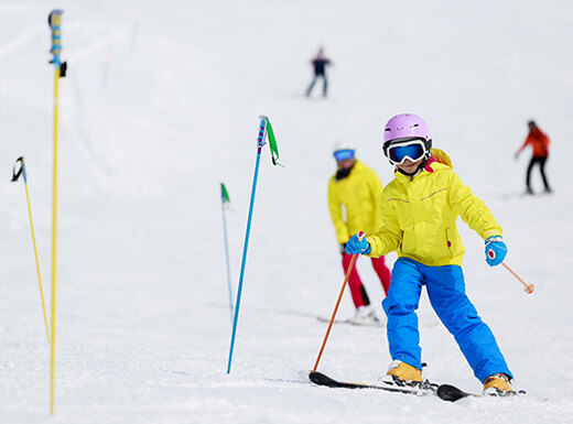 A child wearing a bright yellow coat, bright blue snow pants, and a purple helmet skis carefully down a slope near colorful ski poles at Eldora Mountain near Denver, Colorado.