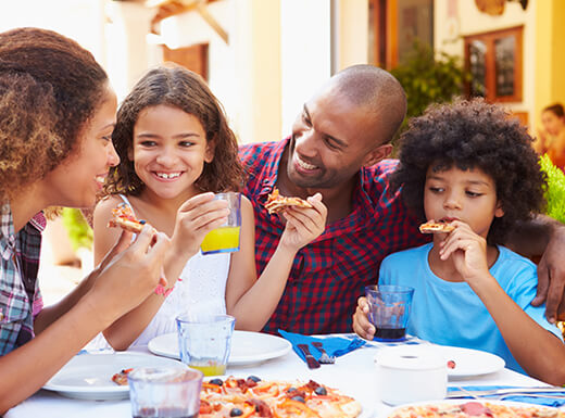 A family of four smiles at one another as they enjoy a pizza lunch together at a restaurant during a family vacation in Denver, Colorado.