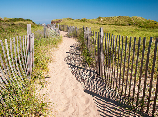 A sandy path with grass and fencing on each side leads towards the beach at Block Island, Rhode Island on a clear, sunny day.