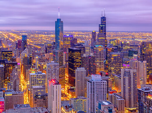 Aerial view of the Chicago skyline at sunset shows iconic skyscrapers and buildings downtown and throughout the city.