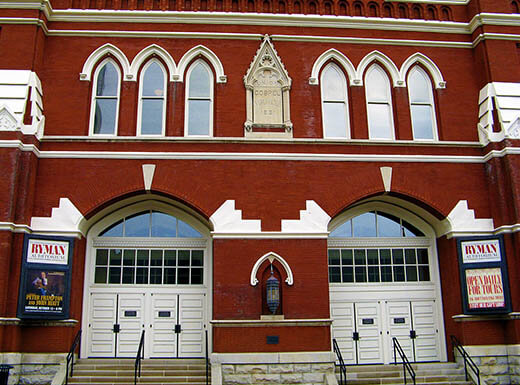An exterior view of the red brick and white trim, historic Ryman Auditorium in Nashville, Tennessee on a crisp afternoon.