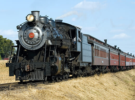 A working steam locomotive at the Strasburg Rail Road in Pennsylvania takes tourists for a scenic ride on a bright summer day.