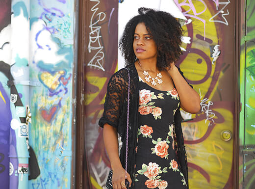 Woman in a floral print dress looking at the graffiti on the wall of Wynwood Kitchen & Bar.