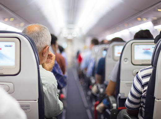 View looking down the aisle of a full airplane with people in seats waiting for plane to takeoff