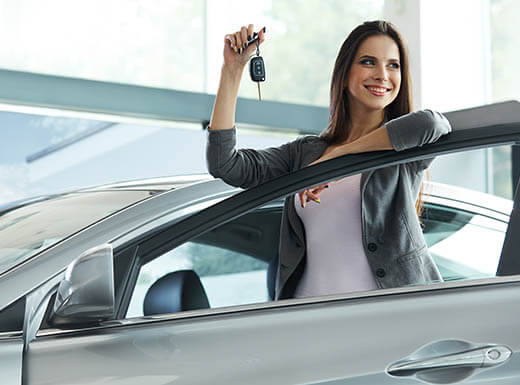 A woman is about to enter her silver rental car while smiling and holding car keys in right hand.