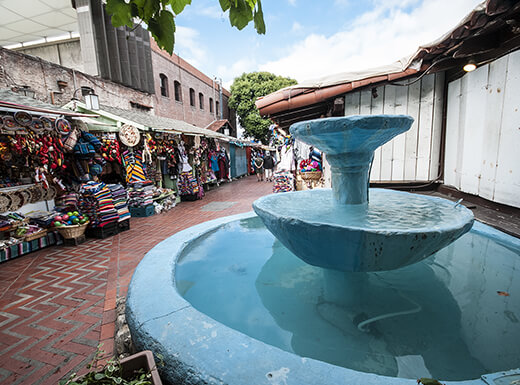 A blue fountain sits along a street of vendors selling handmade goods at the historic Olvera Street Mexican marketplace in Los Angeles.