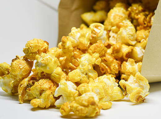 Caramel-covered popcorn spills out of a brown paper bag that is tipped on its side.