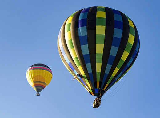 Colorful hot air balloons floating in the sky on a sunny day during the Temecula Village Balloon and Wine Festival.