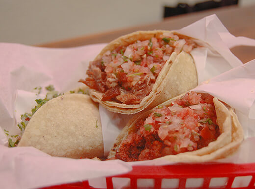 alt= Up close view of three freshly prepared tacos in a red basket.