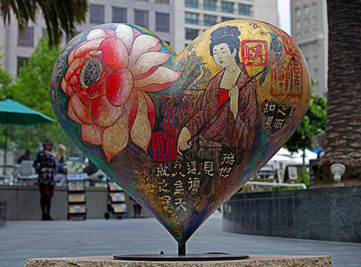 Heart-shaped statue at Union Square in San Francisco, California is painted with various murals and surrounded by city buildings on a cloudy day.